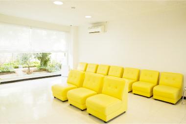 白い部屋に黄色いソファのある明るい待合室
