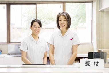 笑顔で受付をする女性スタッフ